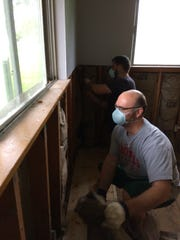 Volunteers Dan and Jeremy remove soiled insulation