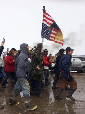 In this Feb. 22, 2017, file photo, people peacefully leave the Dakota Access pipeline main protest camp near Cannon Ball, N.D., as authorities prepare to shut it down in advance of the spring flooding season. As cities and towns host July 4th parades and fireworks shows, some minority residents are expressing mixed feelings about the holiday used to reaffirm the country's founding based on equality and civil liberties.