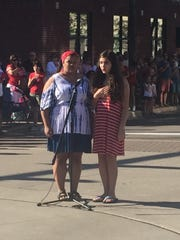 Haley Phillips (left) and Julia Ruggirello of Clarkston kick the parade off with the National Anthem.