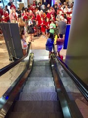 Fans await Alabama coach Nick Saban at the base of the escalator at The Wynfrey hotel in Hoover, Ala., during SEC Media Days.