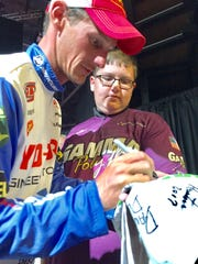 Greenwood angler Brandon Cobb signs an autograph for