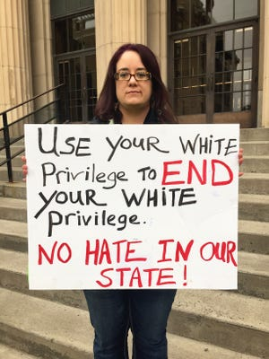"""Use your white privilege to end your white privilege. No hate in our state"" reads a sign held by Laura Wight"