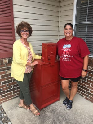 Kathy DiBiase, (left) and Michelle Amadei (right) with the little library at DiBiase Preschool that will dedicated in honor of Special Law Enforcement Officer 1 Charles Amadei, who died in June.