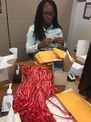 D'Lisa Walker of the Vineland Public Schools registration/transportation department assembles new student ID cards to be issued the first day of school.