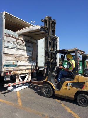 An Oxnard worker fills a truck with recycled mattresses. The city offers a free recycling program for its residents.