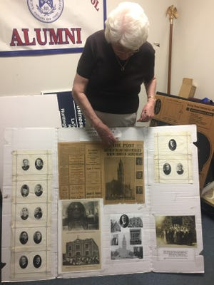 Josephine Walker, the Sacred Heart archivist, prepares a display of vintage items to coincide with the 90th anniversary of Sacred Heart Church on Sunday.