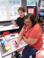 Teacher Lea Marshall keeping track of points awarded as one student swaps his team's score for another group's.