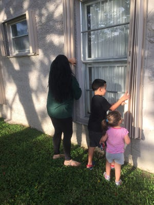 Christina Perez gets some help with storm shutters from 6-year-old Jonathan and 2-year-old Jaslyn