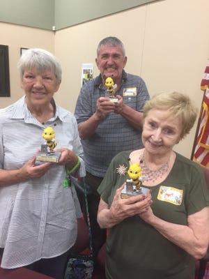 Joann Lessnau, Fred Preston, and Pat Pallesen hold their trophies for placing second, first, and third, respectively, in the 8th Annual Livingston County Senior Spelling Bee on Sept. 20, 2017 in Hartland.