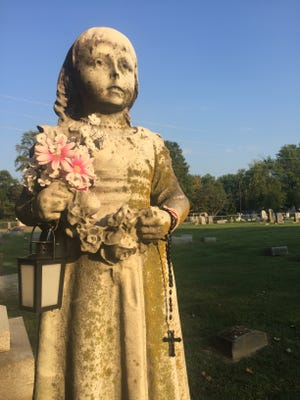 Seen here on September's history walk in Fernwood Cemetery, the gravestone statue of Little Maud Gough, 5, who was burned to death by accident as a child, is still tended by members of her family's church more than a 100 years later.