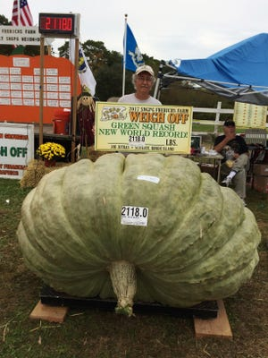 Joe Jutras stands with his world record breaking, 2,118-pound squash, following a weigh-in at Frerichs Farm in Warren, R.I. Jutras has become the first grower in the world to achieve a trifecta in the three most competitive categories in the hobby of growing gargantuan foods, having broken world records for largest pumpkin, longest gourd and now, heaviest squash.