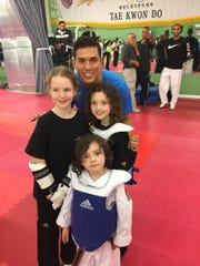Olympic gold medalist Steven Lopez (top) poses with Kai Aceoto, Olivia Lilkeros and Marcus Liljeros at a Taekwondo clinic.