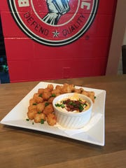Burger Republic's Tator Tot Fondue pairs crispy tots served with four-cheese fondue and topped with bacon bits, chives and sour cream.