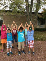 Weston Elementary students practice yoga in their garden.