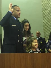 Michael Feaster takes the oath of lieutenant during a promotion ceremony Nov. 8, 2017. He is surrounded by his wife, Danielle, and their daughters, Makenna and Charlotte.