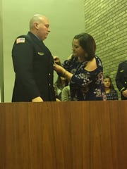 Katie McManus pins a badge to the uniform of her husband, Vineland firefighter Terrence McManus, who was promoted to the rank of lieutenant on Nov. 8, 2017.