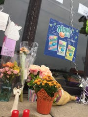 Flowers, cards and balloons sit outside Jump N Jam in Marysville following the Saturday fatal shooting of Cheryl Myny.