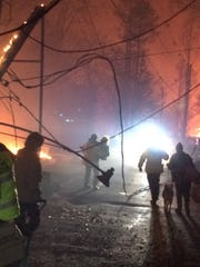 Tennessee Highway Patrol Trooper Stephen Barclay, center, carries Linda Morrow to safety from flames on Baskins Creek Road the night of the Nov. 28, 2016, Gatlinburg wildfire.