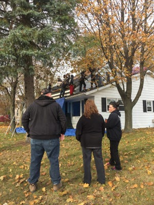 William Little, with Martino Home Improvements, stands with Habitat for Humanity's Robin Yokom and U.S. Navy veteran Michelle Kantz. Crews replaced Kantz's roof Friday as part of the Owens Corning Roof Deployment Project.
