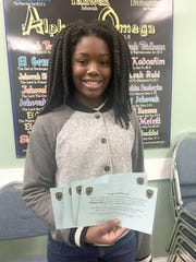 """Gifty Richardson holds up the """"Caught You Being Good"""" citations handed out by the Middletown Police Department to people in the community for doing positive things. The citations were redeemed at Amazing Grace Chapel for a holiday turkey. Richardson, along with her father Frank, handed out turkeys on Monday."""