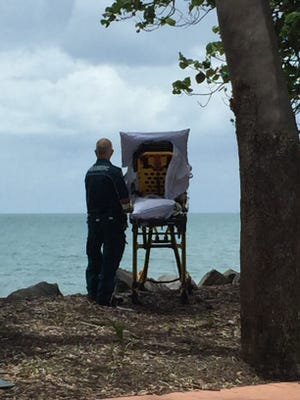 Queensland Ambulance Service paramedic Graeme Cooper stands at a patient's side, overlooking Hervey Bay from a small Australian beachside bluff.