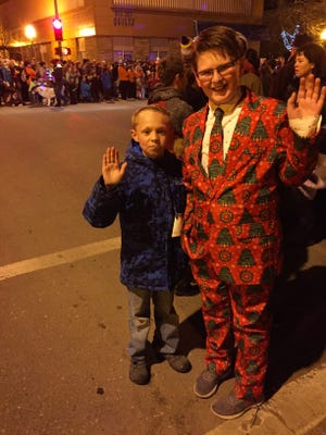 """Tucker Ferguson, 10, and Zach Steenson, 10, wave from the audience in front of the Civic Center during the Parade of Lights. When Zach threw a Vulcan salute, he got a """"Merry Christmas, Live Long and Prosper"""" from a fireman."""