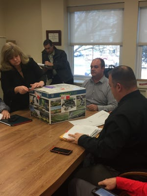 Vineland Public Schools Business Administrator Helen Haley, joined by Keith Salerno, the district's executive director of purchasing, open bids for the Gittone Stadium turf project on Thursday.