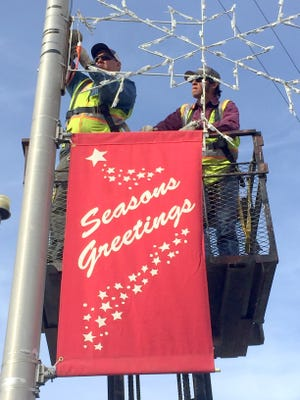 City of Deming work crews were busy Wednesday lining the city streets with Christmas decorations. Each year, the crews put out the street lamp ornaments that bring a festive holiday mood to the city.