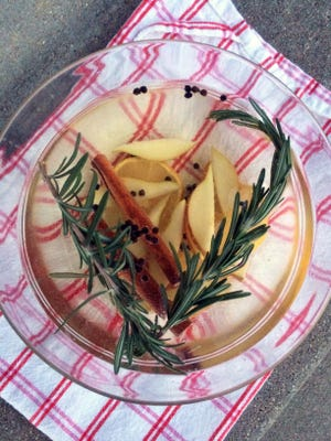White Winter Mulled Wine is garnished with pear and lemon slices and fresh rosemary.