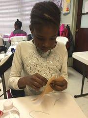 Fourth-grader Ameria Shemelia sews a Creative Critter.