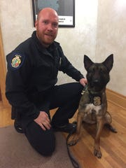 Officer Jon Dailey and Officer Moke at a special council meeting where the K-9 officer was introduced and given his badge.