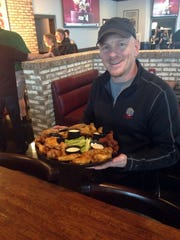 Franchisee Dave McFarland with the popular Wing Sampler plate, which includes 30 wings and five flavors.