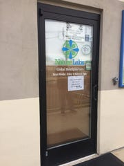 The doors to Nature Labs on North West Avenue in Vineland were locked and covered Friday as employees gathered outside.