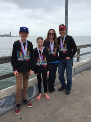 Craig and Bobbi Skrynyk and their two children Noah,15, and Paityn,12, pose at their first Corpus Christi Half Marathon. The Canadian couple have traveled from coast to coast participating in half runs for 11 years.