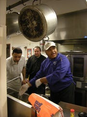 Great Falls Pre-release Center inmate worker, Nathan Lande, and resident, Jeff Vance, get instructions from chef Harold Goode during a demonstration at the center. The Montana Department of Corrections is ending the boot camp program, which had an aftercare program at the Great Falls Pre-Release Services center.