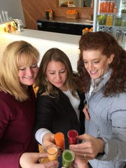 Cathy Vail, Judy Cohen and Jenna Hiller toast with Adena Miller as they drink juice at Just Juice 4 Life.