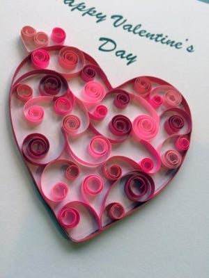Open coil scrolls in various shades of red and pink combine to create a heart-shaped message. Quilling, which involves rolling thin strips of paper into various coil shapes and many other techniques, adds extra elegance to a Valentine's Day greeting.