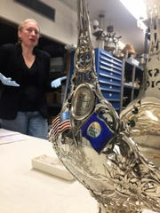 Amanda Trum checks out a silver set that was part of the USS Montana, a Navy ship.