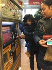 Cousins Collen Chatman of Sicklerville and Lisa Stewart and son Drew of California buy PATCO tickets Wednesday for speedline trips to the Thursday parade.