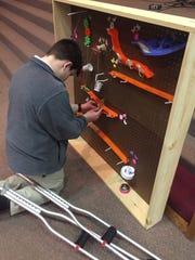 Ninth-grader T.J. Echard preps his device for demonstration at Granville Christian Academy.