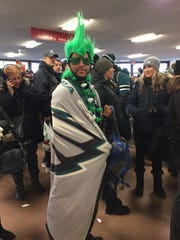 A Philadelphia Eagles fan wraps himself in a team blanket as he waits Thursday at PATCO's Woodcrest station to head into Philadelphia for the parade.