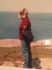 Georgiann standing on the Tintagel cliffs high above