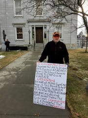 Bert Saldi, of Barre, holds a sign questioning the