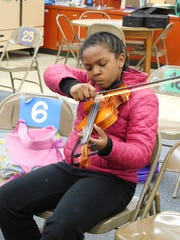 Students concentrate on performing Mozart's Twinkle Twinkle Little Star for the first time.