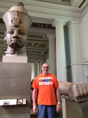 John Gilboe of Plymouth took the D to the British Museum in London. Behind him is a granite statue (1370 BC) of Amenhotep III, also known as Amenhotep the Magnificent,  the ninth Egyptian pharaoh of the Eighteenth Dynasty.  The statue reminded Gilboe of the Joe Louis fist in downtown Detroit.