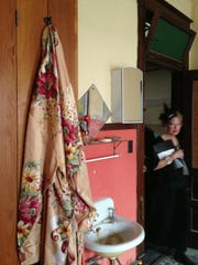 A silky robe hangs from a hook in a former brothel