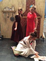 Cinderella (Anne Eddins) cleans the floor while stepsisters
