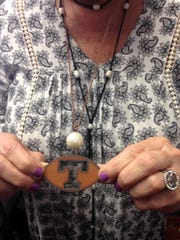Lisa Wallace shows off her popular line of sports jewelry, including this rustic Tennessee pendent cut from tin.