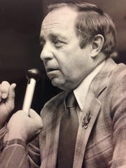 Iowa State football coach Earle Bruce speaks to a reporter