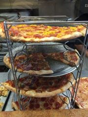 New York-style pizzas are ready to be served at The Pizza Stop in downtown Rochester.